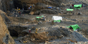 To go with Myanmar-China-mining-economy-politics-resources by Kelly MACNAMARA, Phyo Hein KYAW  This photo taken on October 4, 2015 shows freelance miners at a jade mine in Hpakant, Myanmar's Kachin State. Everyday rickety homes in a remote Myanmar village inch closer to a cliff edge as bulldozers owned by the nation's elite claw the earth beneath them, ravenously hunting jade to feed Chinas multi-billion dollar demand.     AFP PHOTO / Ye Aung THU        (Photo credit should read Ye Aung Thu/AFP/Getty Images)